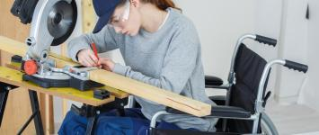 woman in wheel chair with carpenter saw